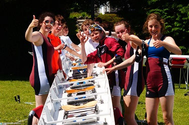 J15 Rowers, at a competition, preparing a crew boat for a race